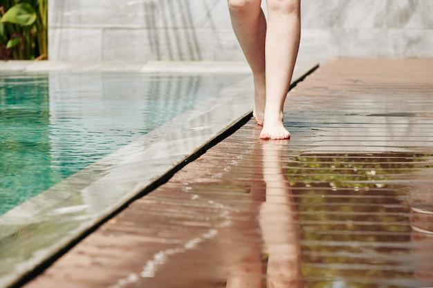 スパホテルのプールの端に沿って歩く女性の足