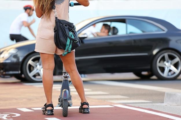 通りを横断するのを待っている自転車専用車線でショートパンツと電動スクーターを持つ女性の足