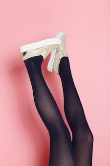黒タイツと黄金の靴の若い白人女性の足