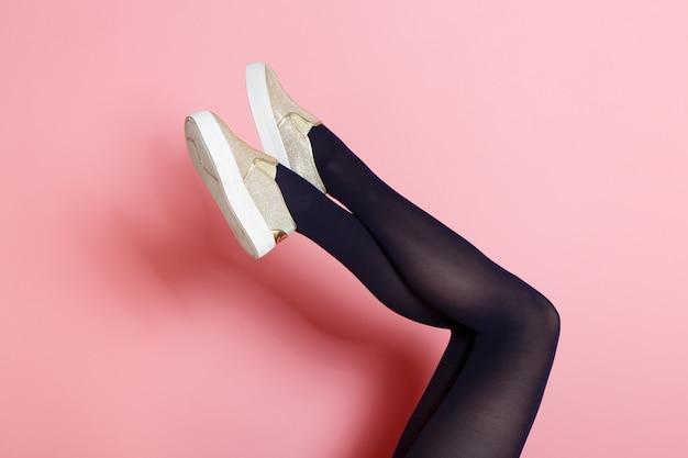 검은 스타킹과 황금 신발에 젊은 백인 여자의 다리