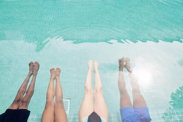더운 여름날에 수영장에서 편안한 젊은 남녀의 다리