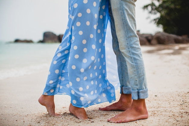 Ноги молодой стильной хипстерской влюбленной пары на тропическом пляже во время отпуска