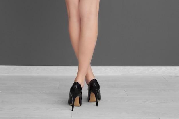 Ноги молодой женщины в туфлях на высоких каблуках, стоящих у серой стены