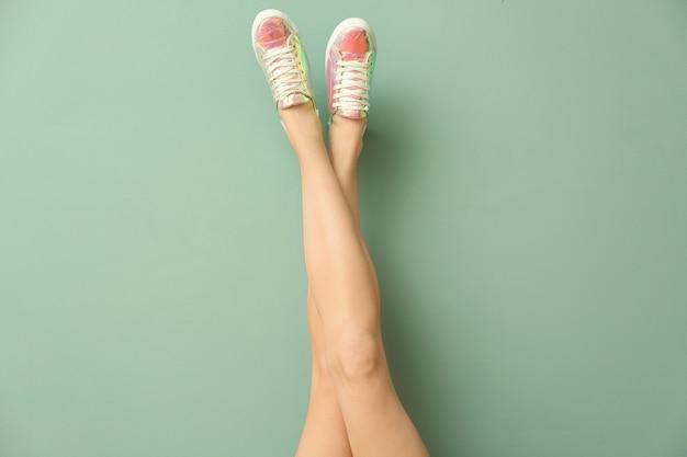 Ноги молодой женщины в стильной повседневной обуви на цвете