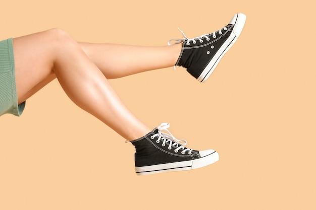 色の背景にスタイリッシュな靴の若い女性の足