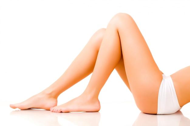 Ноги молодой женщины, изолированные на белом фоне