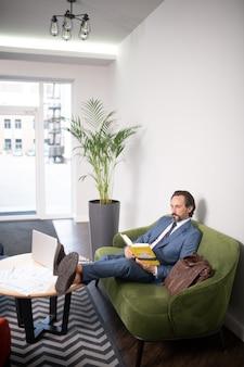 테이블에 다리입니다. 책을 읽고 약간의 휴식을 취하는 동안 테이블에 다리를 올려 놓는 사업가