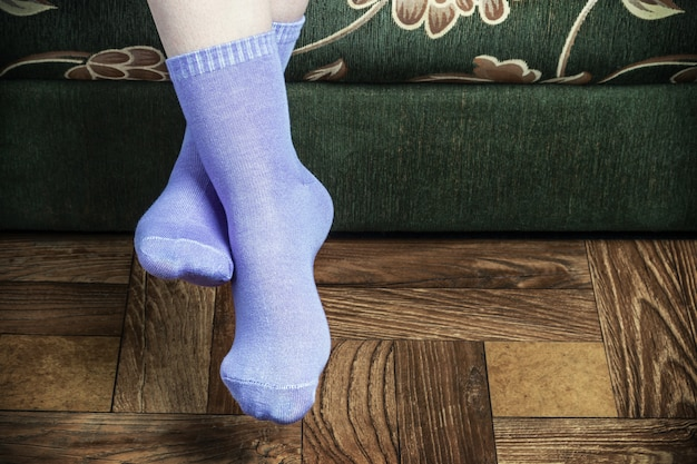 Legs overhang from the sofa in purple socks