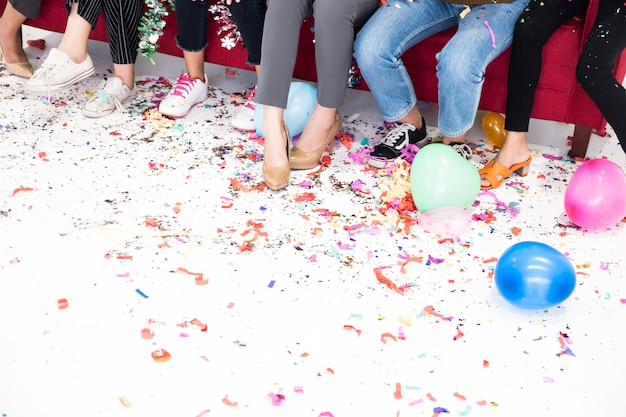 Legs of people sitting on sofa covered with confetti during new year party.