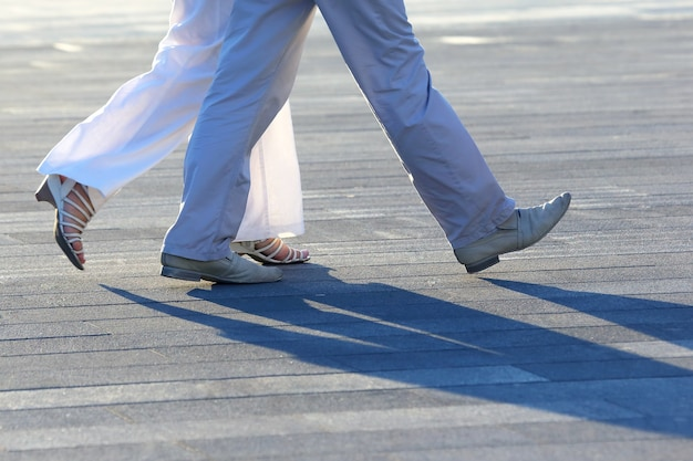 Legs of people walking at sunset