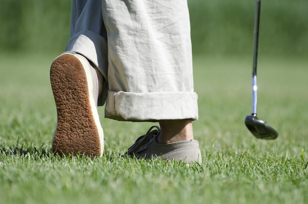 Legs of a person playing golf on the green landscape
