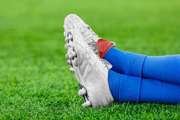 Legs of a player in football on a green lawn