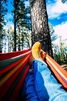屋外のレジャー活動の足の視点と木々の間の森の森のカラフルなハンモックでリラックス-人々とアクティブな自然で健康的なライフスタイルのコンセプト