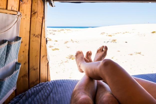 Ноги точки зрения романтической пары в старом фургоне, наслаждающейся пляжем и парковкой у океана вместе
