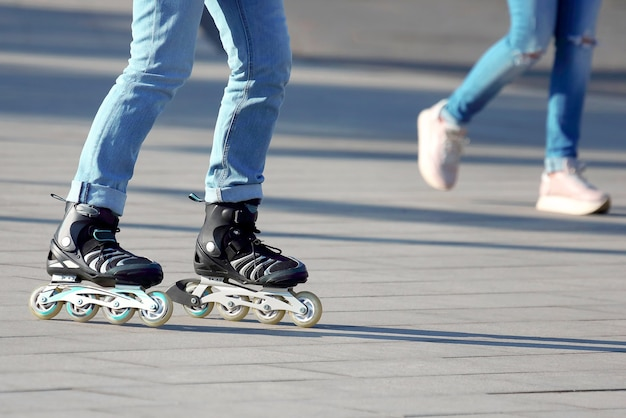 バックグラウンドで歩く人のローラースケートで転がる足。娯楽とレジャー。 10代の若者のスポーツと趣味
