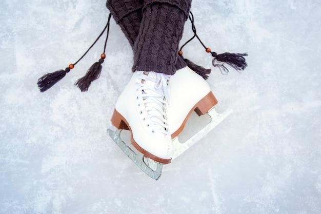 Legs shod with white figure skates. beautiful pose of the legs on the ice rink. warm knit leg warmers with tassels and classic figure skates