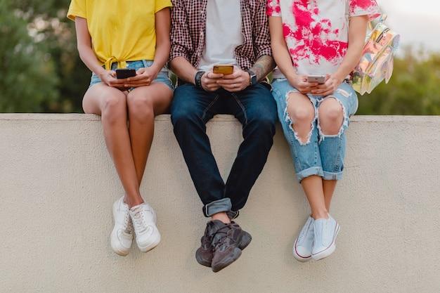 Gambe in scarpe da ginnastica della giovane compagnia di amici seduti nel parco utilizzando gli smartphone