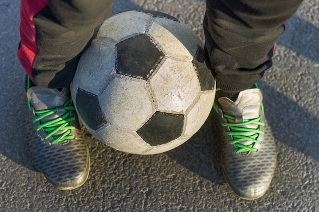 Legs in sportive shoes holding soccer ball outdoors