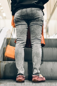 Legs standing on the escalator of a shopping mall
