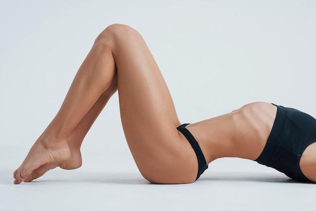 Ноги стоят на пальцах рук. тело молодой женщины с хорошей фигурой фитнеса и черным underview.
