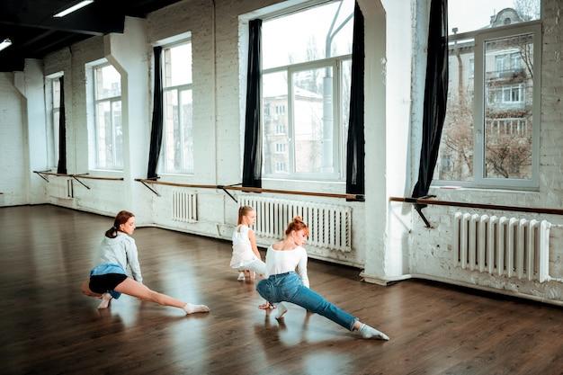 Ноги вытягиваются. рыжая учительница танцев в синих джинсах и ее ученики делают растяжку ног