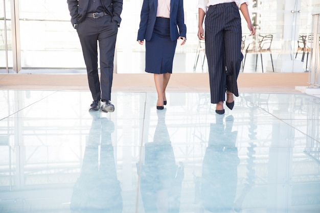 Legs of three business partners walking in office