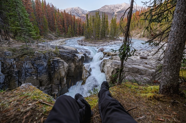 Ноги путешественника сидят и растягиваются на водопаде санвапта в парке ледяных полей в национальном парке джаспер, канада