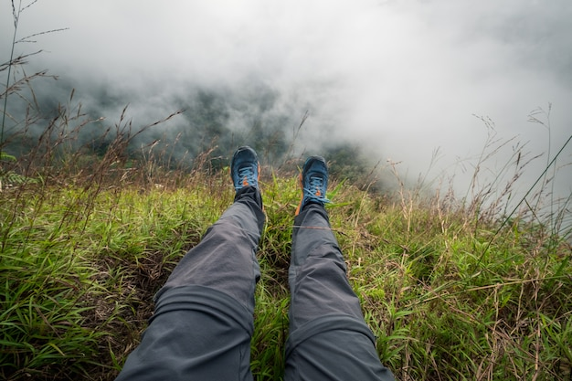 Legs of traveler sitting on a high mountain. freedom concept