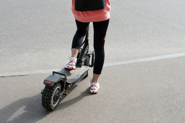 The legs of an unknown girl in white sneakers and gym leggings riding on a black electric scooter over urban asphalt. modern transportation, electric kick scooter.