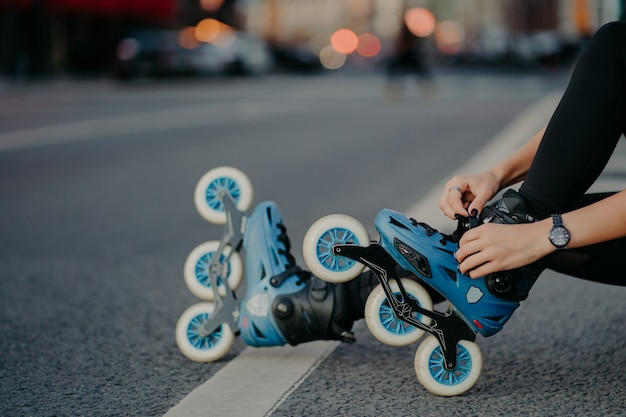 Legs of unrecognizable woman puts on rollerskates going to have exercises outdoor leads active lifestyle poses on street road prepares for inline skating. faceless skater goes in for dangerous sport