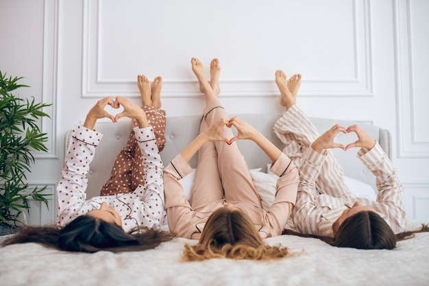 Legs up. three girls lying in bed with their legs up