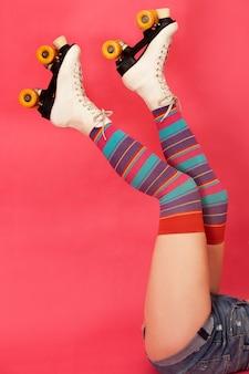 분홍색 배경에 컬러 스타킹과 4륜 스케이트를 신고 다리를 거꾸로