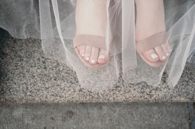 美しいペディキュアの脚優しい夏のペディキュア美しいサンダルでテキストを歩く場所...