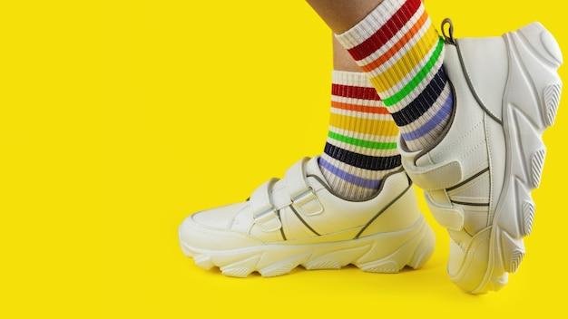 컬러 배경, 클로즈업, lgbtq, 프라이드, 카피스페이스에 흰색 운동화를 신고 무지개를 볼 수 있는 다양한 색상의 양말을 신은 다리