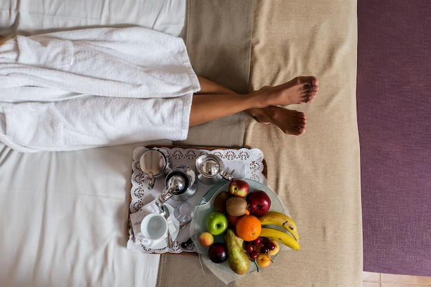 Legs of woman lying on bed with plate of fruits