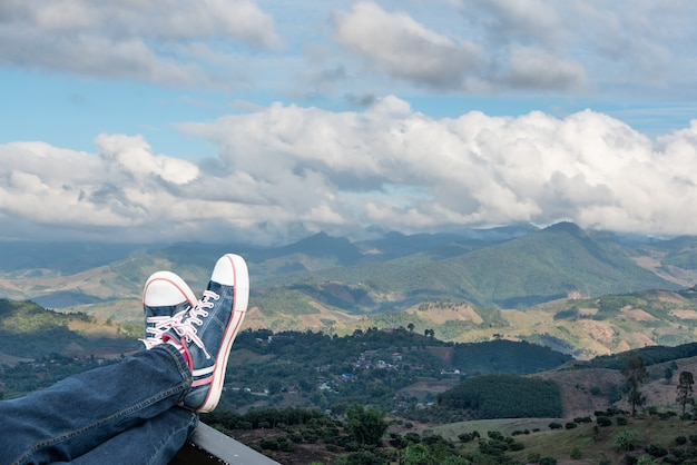 Legs of woman raised up high on beautiful natural mountains background