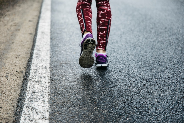 Legs of woman running on road