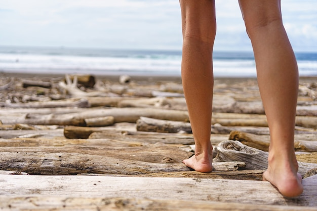 The legs of a woman walking on the beach. jaco beach in costa rica