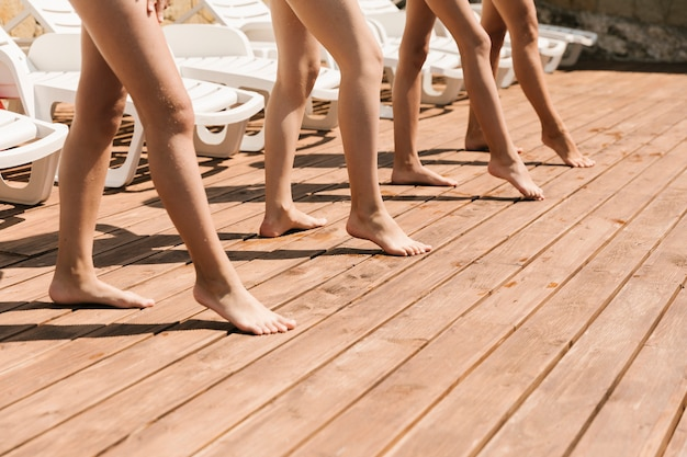 Legs on wooden floor at swimming pool