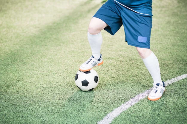 Legs of young active female player in blue uniform keeping right foot on soccer ball during game of football on the field