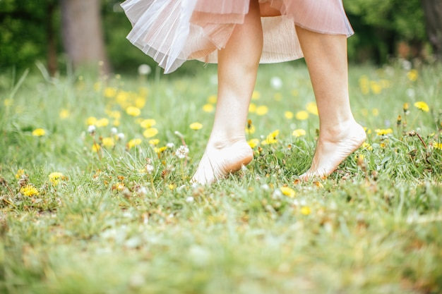Legs of young barefoot women wearing pink dress standing on one leg on green grass with yellow flowers, close up