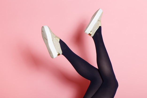 Legs of young caucasian woman in black tights and golden shoes