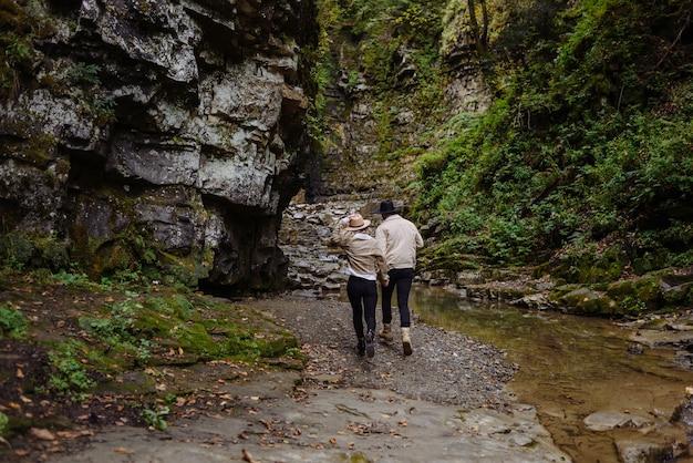 石に行く足の若いカップル。全長。岩を背景に後ろから見た男女の眺め。古い工業用花崗岩採石場の風景。