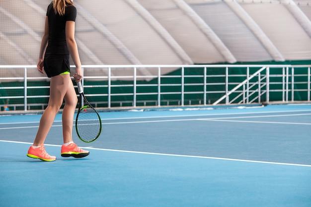 Gambe della ragazza in un campo da tennis chiuso con palla e racchetta