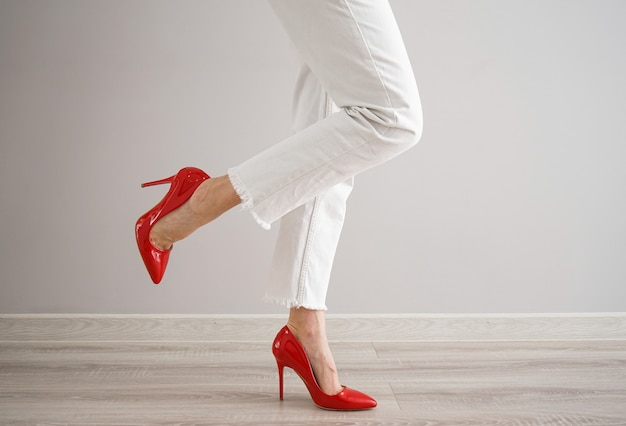 Legs of a young girl in white jeans and red shoes on gray background.