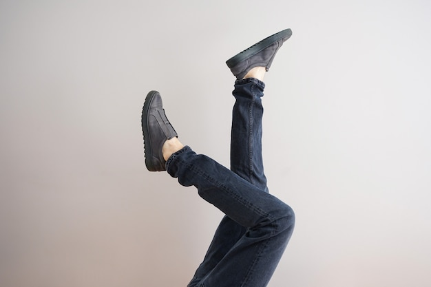 Legs of a young man in jeans and shoes on a gray background.