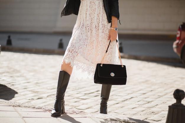 Gambe di giovane donna graziosa in stivali che camminano in strada in abito alla moda, tenendo la borsa, indossando giacca di pelle nera e abito di pizzo bianco, stile primavera autunno