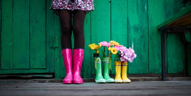 Legs of young woman in black tights, skirt with floral print and pink rubberboots standing against green painted wall or fence outside