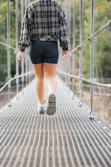 Legs of a young woman crossing a bridge