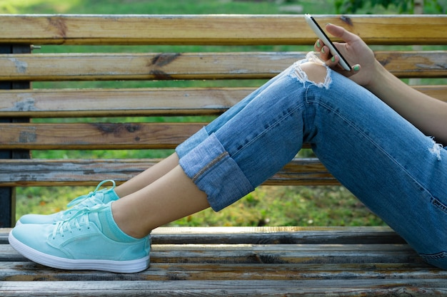 Legs of a young woman in jeans on a bench in the park